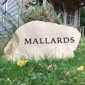 House sign sandstone boulder black letters