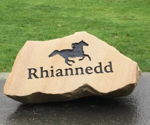 pet memorial boulder in sandstone with running horse motif and inscription painted black for rhiannedd