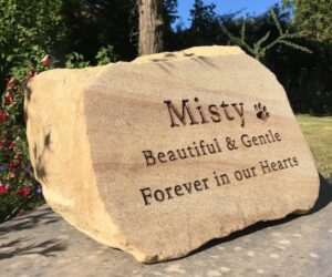 sandstone pet memorial boulder with brown inscription and pawprint motif for Misty in the gardens