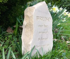 sandstone column pet memorial with unpainted letters for Bruno in the garden